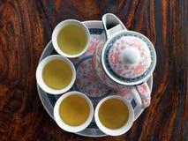 Juego de té del estampado de plores en la tabla de madera en ángulo superior un sistema de la taza y del pote Imágenes de archivo libres de regalías