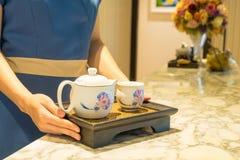 Juego de té en las manos del massager fotografía de archivo