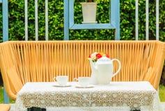 Juego de té en una tabla en un pequeño jardín Foto de archivo