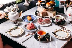 Juego de té inglés de la tarde incluyendo té caliente, pasteles, scones, bocadillos y mini empanadas en la tabla superior de márm imagen de archivo libre de regalías