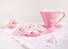 Juego de té rosado con las galletas en un fondo blanco imagen de archivo libre de regalías