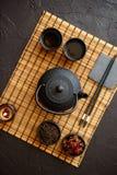 Juego de té verde asiático en la estera de bambú imagen de archivo libre de regalías