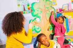 Juego del alfabeto del juego del profesor con los niños en cuarto de niños imagenes de archivo