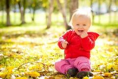Juego del bebé con el brench de madera bajo árboles en parque Fotografía de archivo