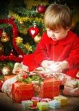 Juego del bebé con la actual caja en el árbol de navidad Fotografía de archivo