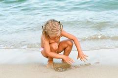 Juego del bebé en la playa. Imagen de archivo