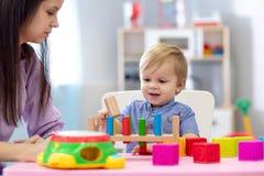 Juego del bebé y del cuidador del cuarto de niños en la tabla en centro de guardería fotografía de archivo