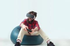 Juego del hombre con el gamepad y las gafas de VR Imágenes de archivo libres de regalías
