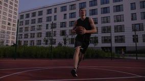Juego del hombre en streetball en el patio urbano de la puesta del sol