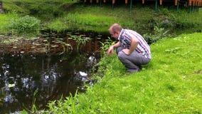 Juego del hombre joven con la nave del papel hecho a mano cerca del río almacen de metraje de vídeo
