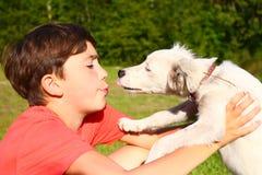 juego del muchacho con el perrito blanco en el fondo del país del verano Fotografía de archivo