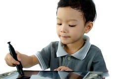 Juego del muchacho con PC de la tableta Imagen de archivo
