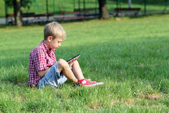 Juego del muchacho con PC de la tableta Fotografía de archivo libre de regalías