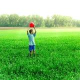 Juego del muchacho con una bola Fotos de archivo
