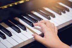 Juego del muchacho el piano con el foco selectivo a la llave y a las manos del piano foto de archivo libre de regalías
