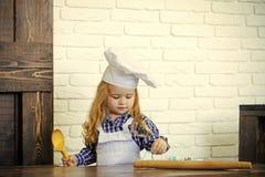 Juego del niño Cocinero del muchacho en sombrero del cocinero y delantal en cocina Imágenes de archivo libres de regalías