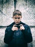 Juego del niño con el teléfono móvil Foto de archivo