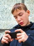 Juego del niño con el teléfono móvil Fotos de archivo libres de regalías
