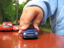 Juego del niño pequeño con el juguete-coche Fotografía de archivo