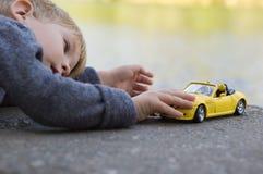 Juego del niño pequeño con un coche Imágenes de archivo libres de regalías