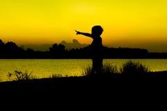 Juego del niño pequeño y finger del punto en la puesta del sol del río Imagen de archivo libre de regalías