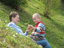 Juego del niño y de la madre en hierba Fotografía de archivo libre de regalías