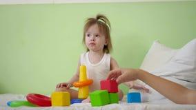 Juego del niño y de la mamá con los cubos coloridos en cama Juguetes educativos para los niños del preescolar y de la guardería J almacen de metraje de vídeo