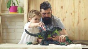 Juego del padre y del hijo con los juguetes Familia, niñez, actividad y concepto de la gente Padre feliz y pequeño hijo que juega almacen de video