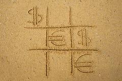 juego del Tic-TAC-dedo del pie con jugar símbolos del euro y del dólar en la arena Imágenes de archivo libres de regalías