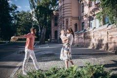 Juego elegante feliz de los padres con el hijo Permanecen en la calle soleada de la mañana, momento asombroso de la familia día d Fotos de archivo