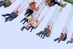 Juego feliz de la gente en un parque de atracciones Fotografía de archivo libre de regalías