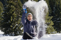 Juego feliz del hombre del adolescente con nieve en chaqueta que lleva de invierno Fotos de archivo