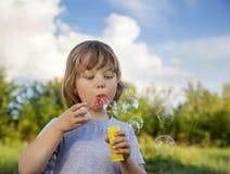 Juego feliz del muchacho en burbujas Fotos de archivo libres de regalías