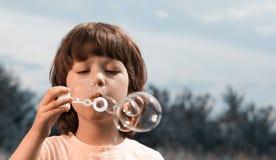 Juego feliz del muchacho en burbujas al aire libre foto de archivo libre de regalías