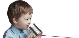 Juego feliz del muchacho en el teléfono de la lata imagenes de archivo