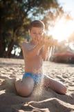 Juego feliz del niño con la arena en la playa; Foto de archivo