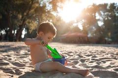 Juego feliz del niño con la arena en la playa; Foto de archivo libre de regalías