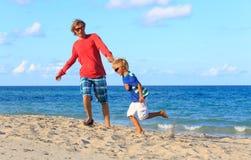 Juego feliz del padre y del hijo en la playa Foto de archivo libre de regalías