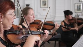 Juego femenino de los violinistas en los instrumentos musicales y mirada en la hoja de papel con las notas musicales sobre concie almacen de metraje de vídeo