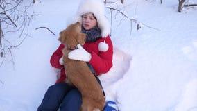 Juego hermoso de la muchacha y del perro en nieve acumulada por la ventisca el niño con el perro de caza que camina en invierno e metrajes