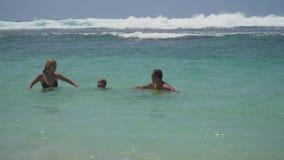 Juego joven de la familia en el mar almacen de metraje de vídeo
