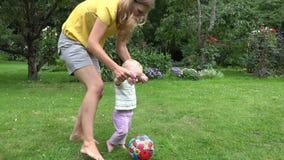 Juego joven de la madre con el bebé con la bola en jardín del verano 4K metrajes