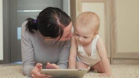 Juego joven de la madre y del bebé en la tableta en una alfombra en el piso Madre e hijo que se divierten con una tableta digital metrajes