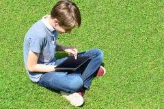 Juego joven del muchacho en su nueva PC de la tableta Imagenes de archivo