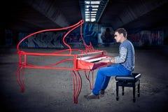 Juego joven del pianista en su piano con emociones brillantes, Fotografía de archivo libre de regalías