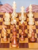 Juego medio - el jugador piensa sobre la posición respecto a tablero de ajedrez foto de archivo