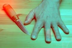 Juego peligroso Cuchilla del cuchillo entre los fingeres en el fondo de una tabla de madera fotos de archivo