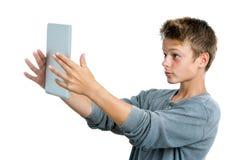 Juego que juega adolescente en la tableta. Fotos de archivo
