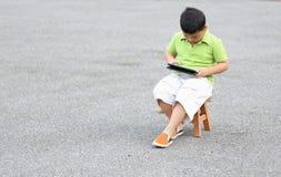 Juego que se sienta del muchacho una tableta Imagenes de archivo