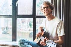 Juego sonriente feliz del hombre joven en la guitarra cerca de la ventana Imagen de archivo libre de regalías